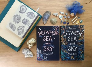 Notebooks, proof, finished book for Between Sea and Sky, surrounded by lots of shells and beachcombing treasures.
